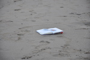 Quaderno e penna sulla spiaggia